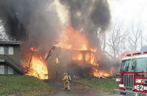 A firefighter walks up a driveway as an apartment building burns in Akron, Ohio, where authorities say a small business jet crashed yesterday. (PHOTO:AP)