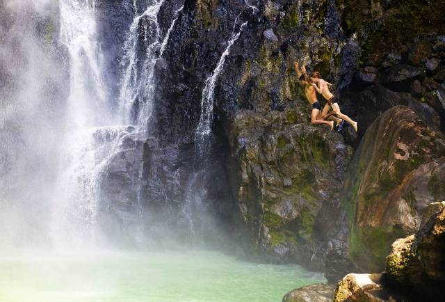 Two people jump into the pool at the foot of Victoria Falls near Delices, Dominica © Nick Ledger / Getty Images